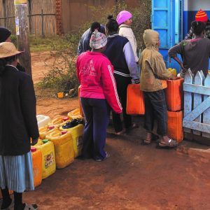 Tana residents queue for water from a water kiosk