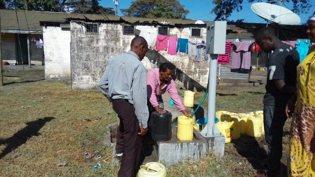 Customers using a newly pre-paid water dispenser in Nakuru