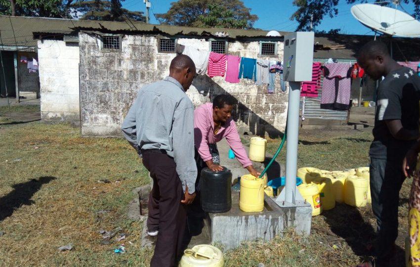 Customers using a newly pre-paid water dispenser in Nakuru