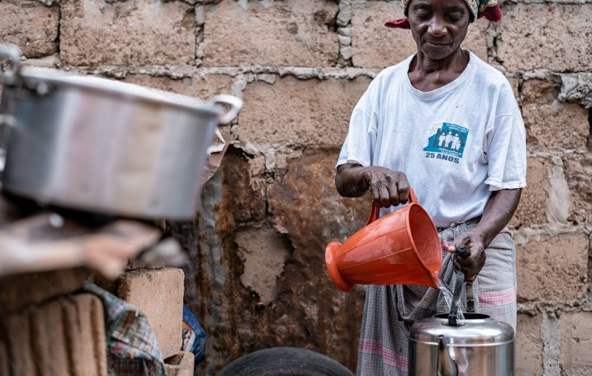 Adelaide Massingue collecting water to prepare her food