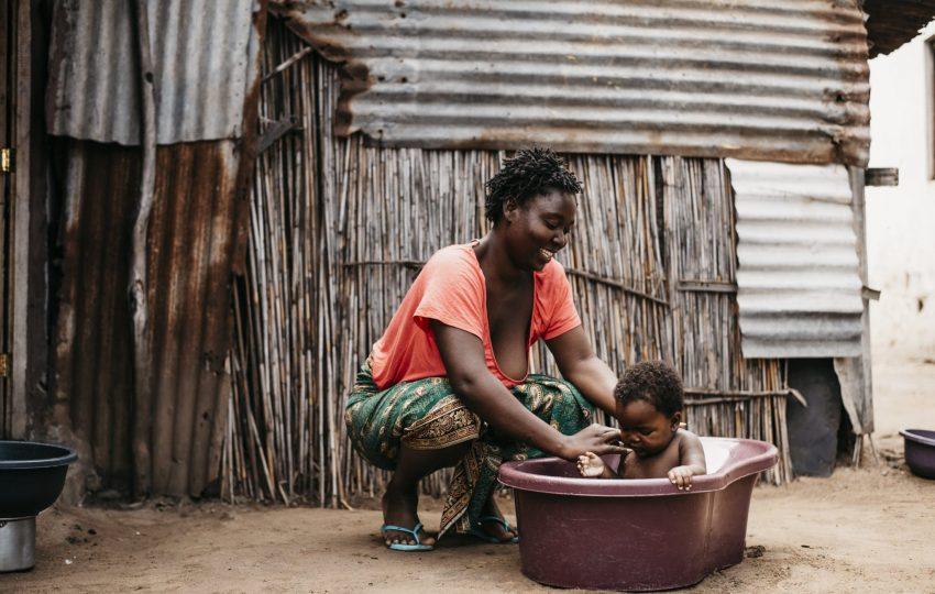 Nélia António washes her child in Maputo